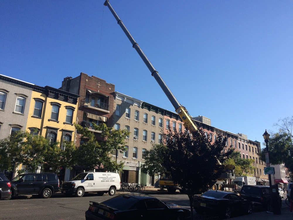 The crane that has to air lift the hood system onto the roof
